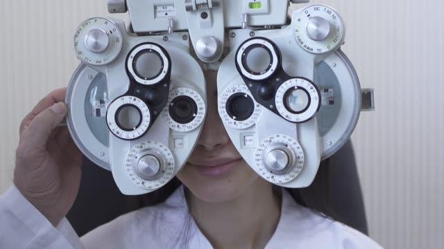 vidéos et rushes de examen des yeux de jeune femme à l'ophtalmologiste optométriste fermer. - réfracteur