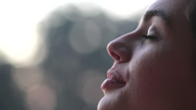 ung kvinna ansikte öppna ögon i meditation och kontemplation loooking upp på himlen med hopp och tro - bekymmerslös bildbanksvideor och videomaterial från bakom kulisserna