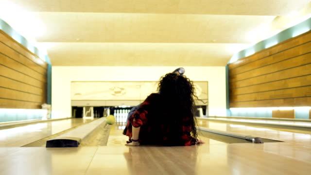 young woman falls down while throws a bowling ball - niedoskonałość filmów i materiałów b-roll
