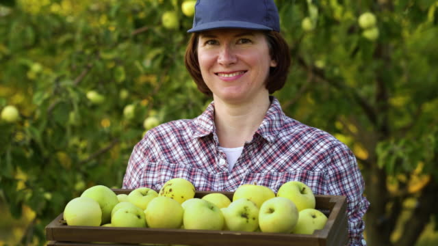 Young woman farmer smiling at camera with box of apples video