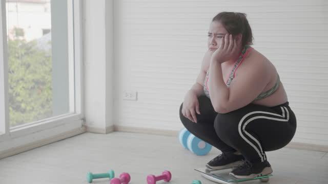 若い女性の脂肪は、自宅でスケールを測定した後に動揺を感じます, 体重減少に不満を持っている間、太りすぎのストレスと心配を持つ女性, プラスサイズ, 肥満とカロリー, コントロール体� - 体への関心点の映像素材/bロール