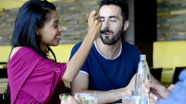 Young woman feeds salad to man Closeup shot of young woman feeds salad to her boyfriend. Friends having meal together. Happy young friends eating salad at restaurant. fork stock videos & royalty-free footage