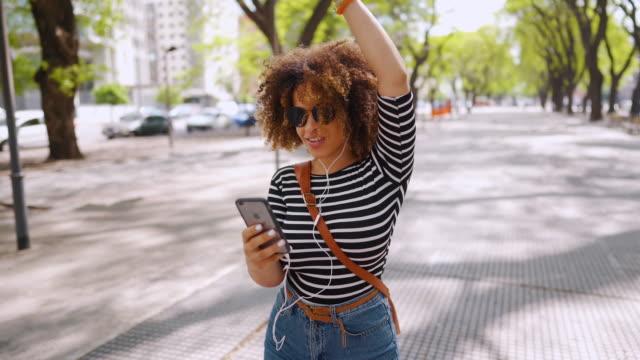 stockvideo's en b-roll-footage met jonge vrouw die gelukkig voelt terwijl het luisteren en het zingen van haar favoriete lied in openlucht - street style