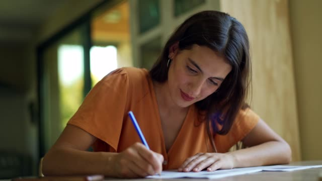 young woman filling in paperwork - scrivere video stock e b–roll