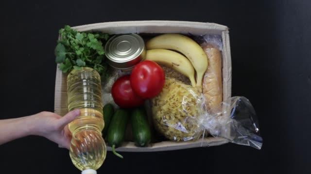 vídeos y material grabado en eventos de stock de una joven llena una caja con comida. la caja para donaciones de alimentos. entrega de alimentos. - food drive