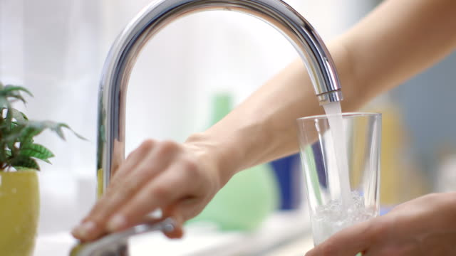 Young woman fills glass under running tap in kitchen. Studio Shot, Professional Lighting, Shallow DOF. CU of a woman filling a glass of water faucet stock videos & royalty-free footage