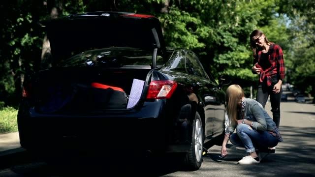 vídeos de stock e filmes b-roll de young woman fixing flat tyre with jack on road - berma da estrada