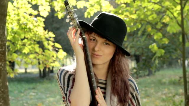 若い女性がサーフボード、公園にポーズを取る、ギター、笑顔をお過ごしください。 ビデオ