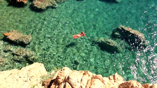 young woman floating on pool mattress in the ocean - sardegna video stock e b–roll