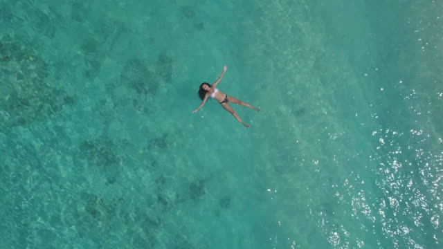Young Woman Floating on Water Near Gili Island Coastline Young Woman Floating on Water Near Gili Island Coastline. floating on water stock videos & royalty-free footage