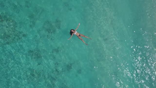 vídeos de stock, filmes e b-roll de mulher nova que flutua na água perto do litoral do console de gili - flutuando na água