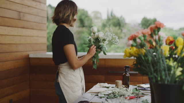 young woman florist preparing flower bouquet - bouquet video stock e b–roll