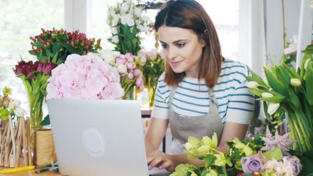 ung kvinna florist arbetar online. - blomstermarknad bildbanksvideor och videomaterial från bakom kulisserna