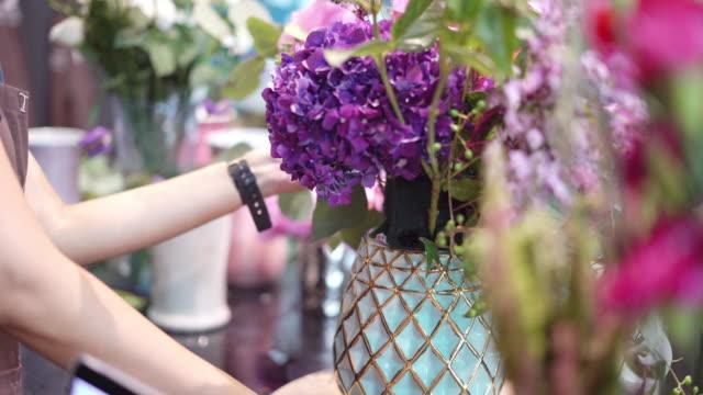 vidéos et rushes de fleuriste de jeune femme travaillant avec des fleurs. - composition florale