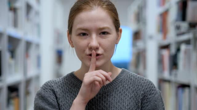 young woman gesturing  silence, finger on lips, indoor - cisza filmów i materiałów b-roll
