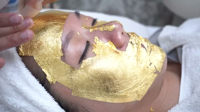 young woman getting 24 karat gold facial treatment at the beauty clinic. the treatment of using real gold for youthful skin - spa facial stock videos & royalty-free footage