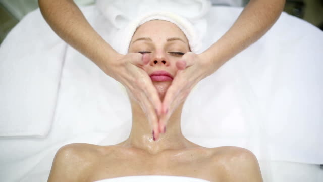 Young woman getting a facial massage at spa salon video