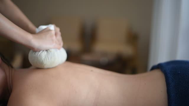 Jeune femme de faire un massage thaï herbal compress au salon spa. - Vidéo
