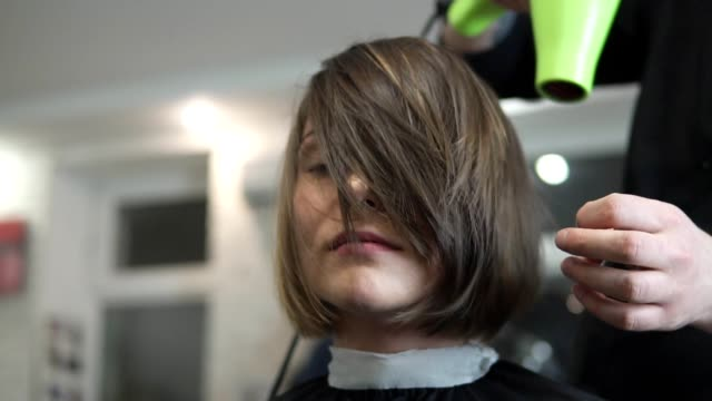 Young woman getting her hair dressed in beauty salon video