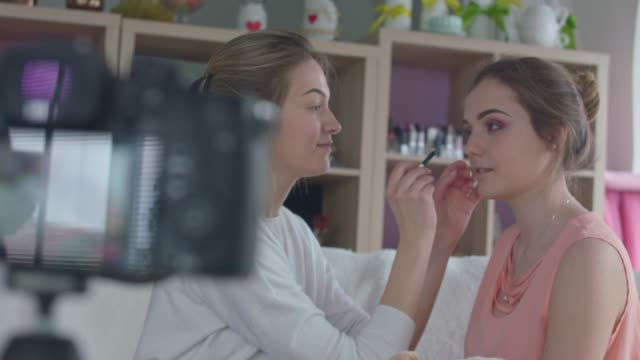 Young woman getting her make up done by a beauty blogger while filming a video Selective focus of a smiling young woman sitting down and relaxing while getting her make up done by a beauty blogger who is filming a video tutorial for her internet and social media audience. beautician stock videos & royalty-free footage