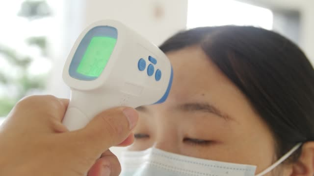 Young woman getting her temperature test
