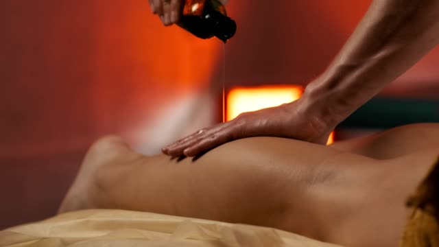 Young woman getting legs massage with oil in resort spa salon. Evening light.