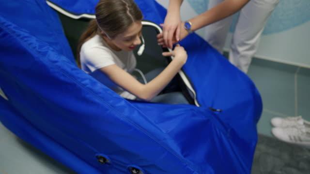 junge frau steigt aus der hyperbarischen sauerstoffkammer aus - reliability stock-videos und b-roll-filmmaterial