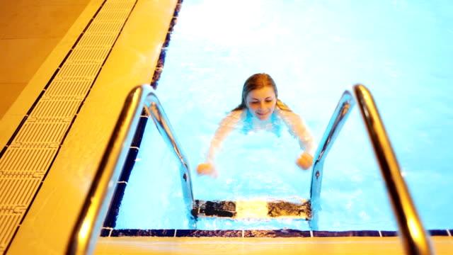 Joven mujer levantarse de la piscina. - vídeo