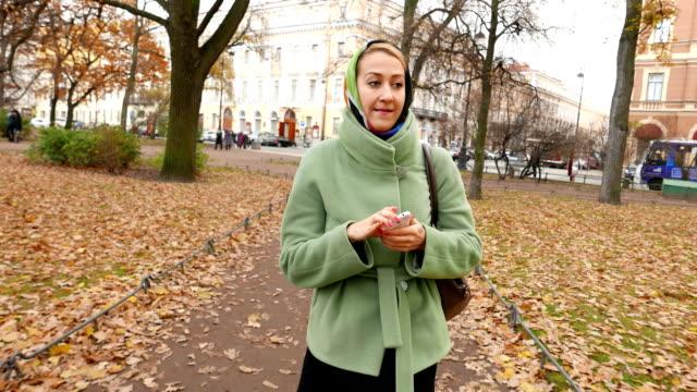 vidéos et rushes de jeune femme aller et utiliser le smartphone, marcher dans le parc automne. - étudiant(e)