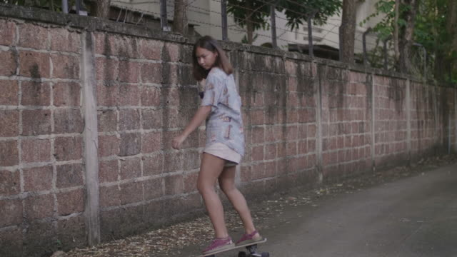 A young woman goes longboard skateboarding at home.