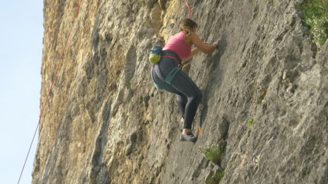 CLOSE UP: Young woman goes rock climbing up a mountain in Slovenian countryside.