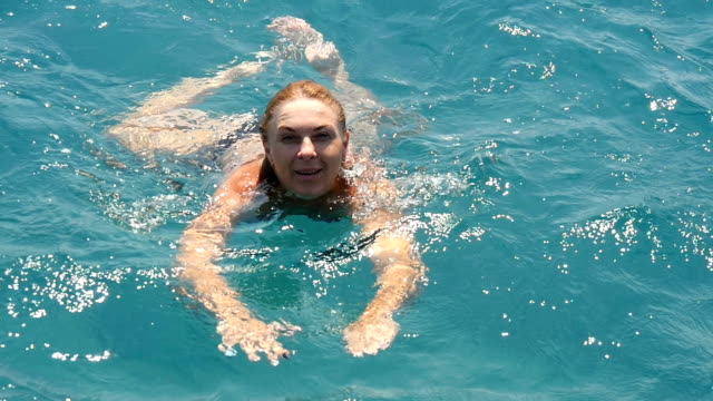 Young woman goes sea-bathing in turquoise waters of the Aegean Sea in slo-mo video