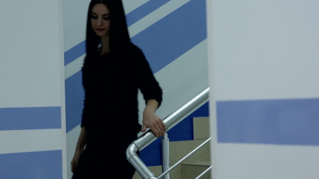 young woman going downstairs holding on to the banister - parapetto barriera video stock e b–roll