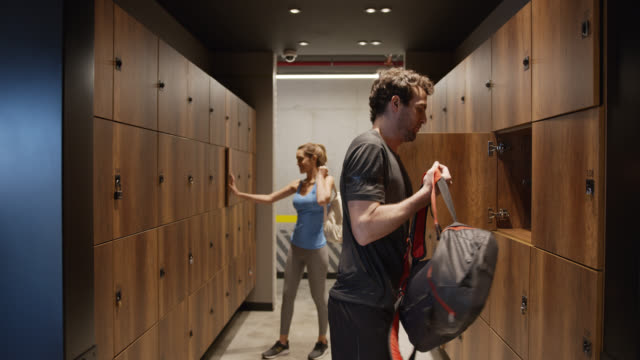 Young woman grabbing her stuff from mixed locker room while man leaves his belongings in locker Young woman grabbing her stuff from mixed locker room while man leaves his belongings in locker - Healthy lifestyles locker stock videos & royalty-free footage