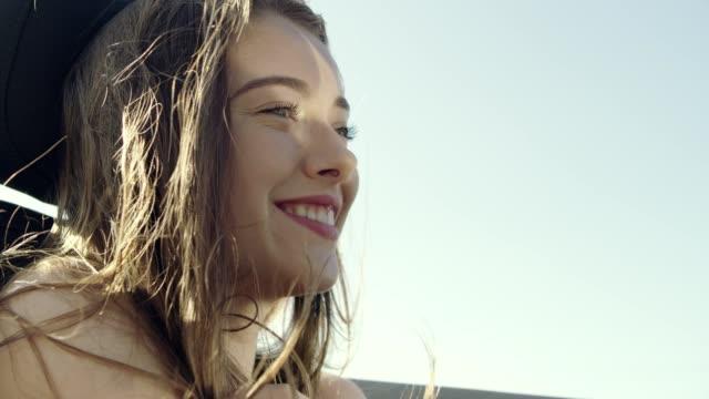 young woman hair blowing in wind while riding in cabrio car - długie włosy filmów i materiałów b-roll