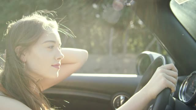 Young woman hair blowing in wind while riding in convertible car Young happy woman driving a car, relax time red lipstick stock videos & royalty-free footage