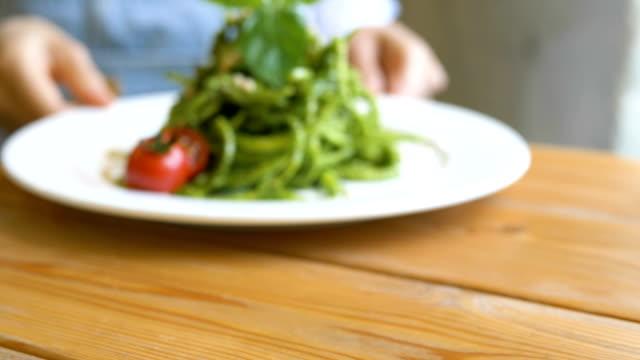 young woman hands move white plate with green fresh salad - gotowy do jedzenia filmów i materiałów b-roll