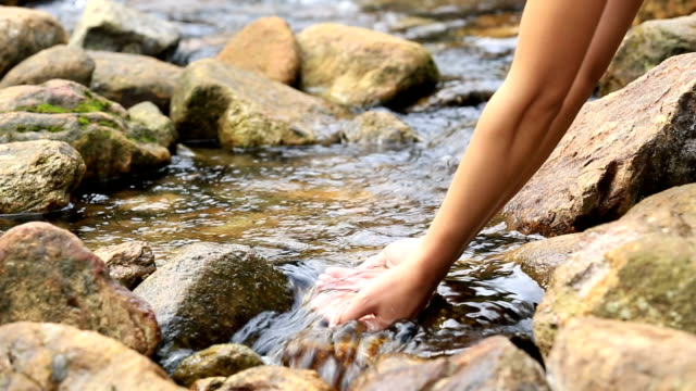 young woman hands with the stream water video