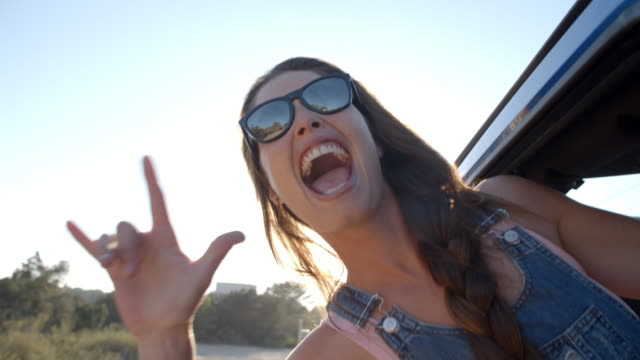 Young woman hanging out of a car window during a road trip video