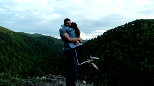a young woman happily hugs her boyfriend standing on top of a mountain. - mountain top filmów i materiałów b-roll