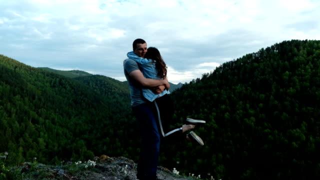 한 젊은 여성이 산 꼭대기에 서 있는 남자친구를 행복하게 껴안습니다. - mountain top 스톡 비디오 및 b-롤 화면