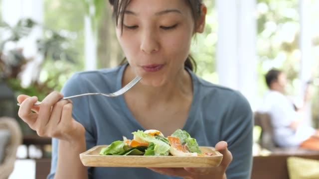 若い女性の幸せな顔を食べるサラダハッピーフェイス、ヘルシー食べる - ベジタリアン料理点の映像素材/bロール