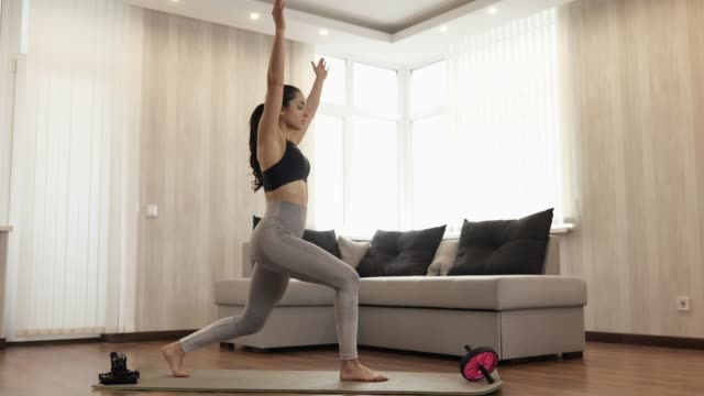 Young woman has workout at home during quarantine. Stand straight on yoga mat and taking warrior asana position on one leg squat with hands up. Taking exercise and bodycare.