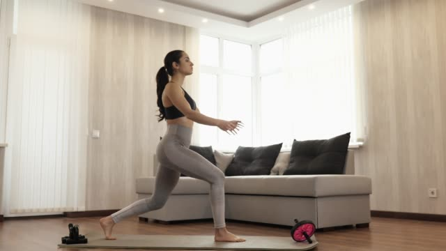Young woman has workout at home during quarantine. Stand straight on yoga mat and taking one leg squad or warrior asana position. Calm peaceful and concentrated.