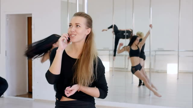 Young woman have a phone call during a pole dance class video