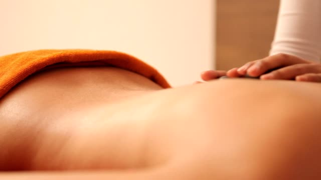 Young woman having a stone massage video