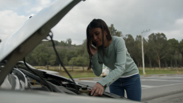 Young woman having car trouble calling for road side assistance