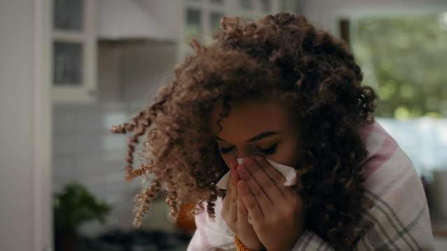 vídeos y material grabado en eventos de stock de mujer joven que tiene gripe y se sopla la nariz en el pañuelo - flu