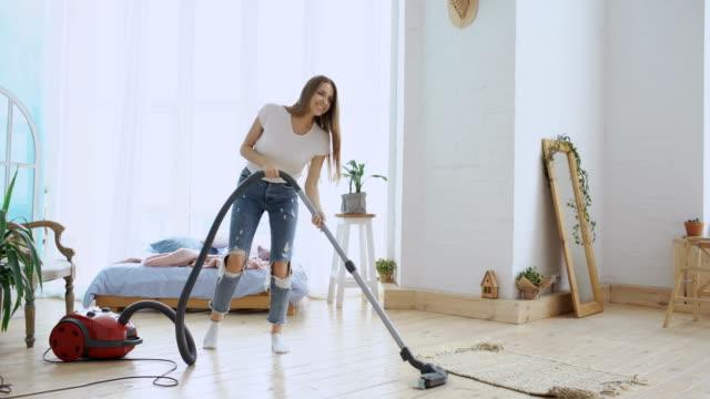 Junge Frau, die Spaß Hausputz mit Staubsauger tanzen und singen zu Hause – Video