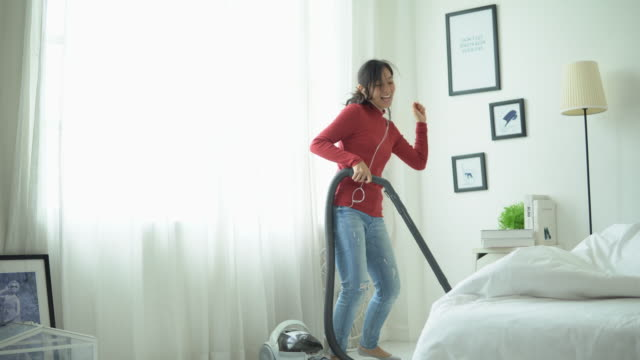 Young woman having fun cleaning house with vacuum cleaner Thailand, Cleaning, Vacuum Cleaner, Dancing, Music hovering stock videos & royalty-free footage